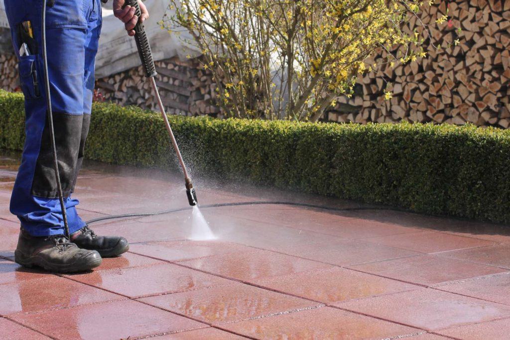 man pressure washing pavers