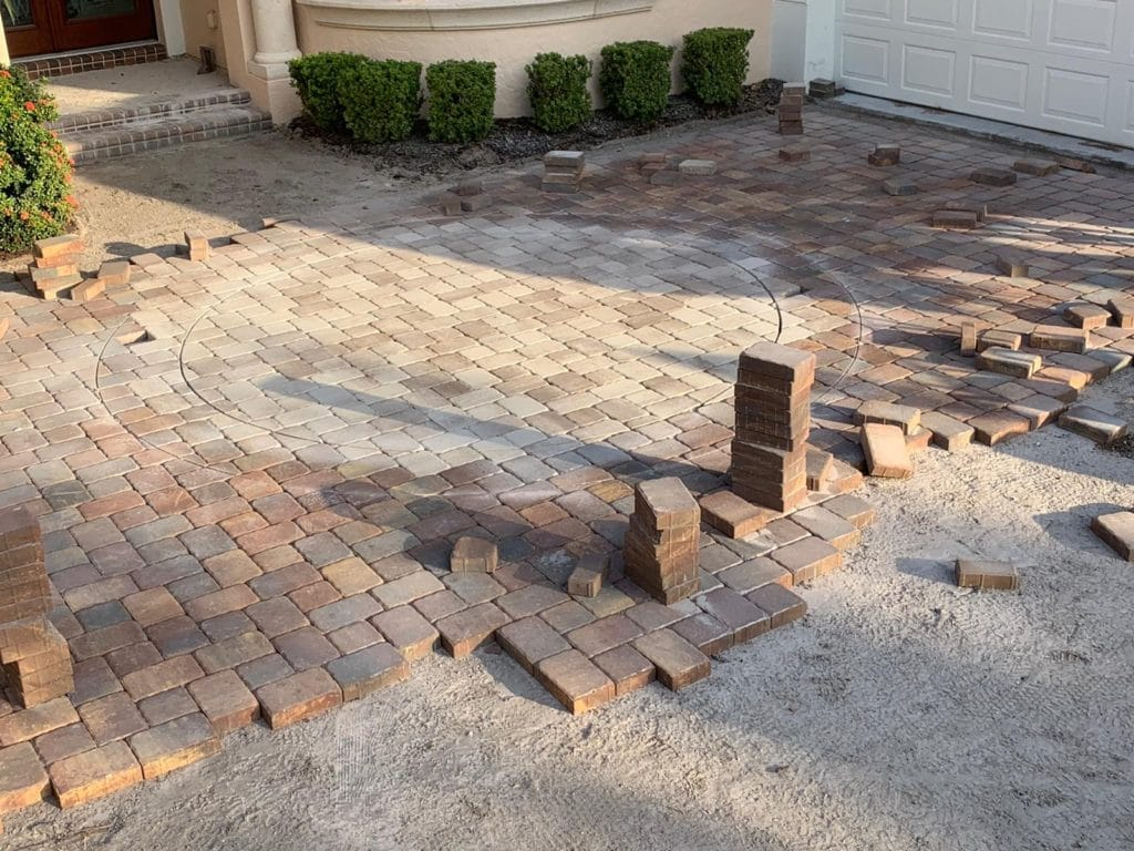 Brick pavers being installed in a bed of sand in front of a house