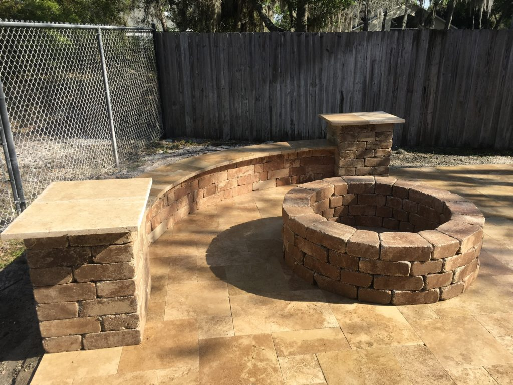 Fire pit made of pavers surrounded by a patio and a paver bench in the front of a fence