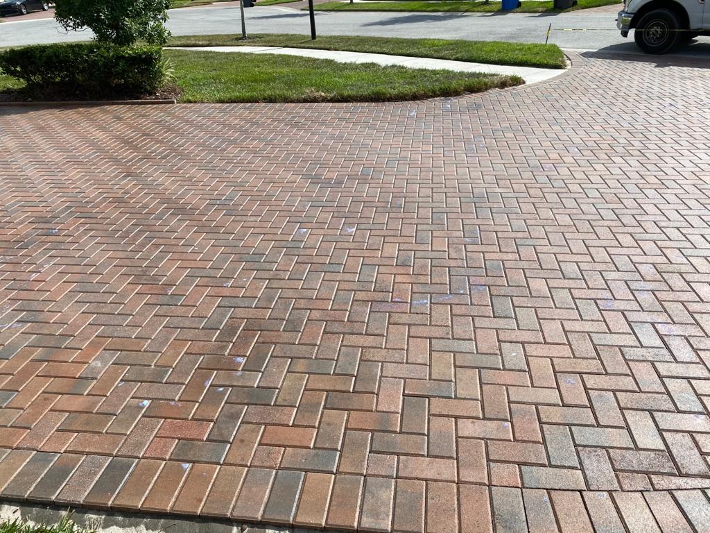 A brick paver patio in a herringbone pattern