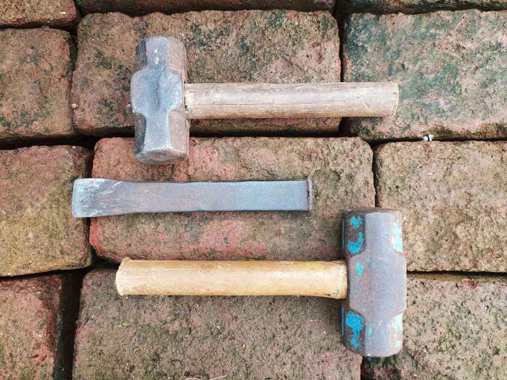 Two hammers and a chisel on an old stone paver background.