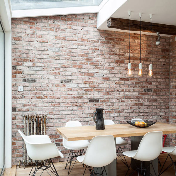 Whitewashed wall of bricks with a set of table and white chairs upfront.