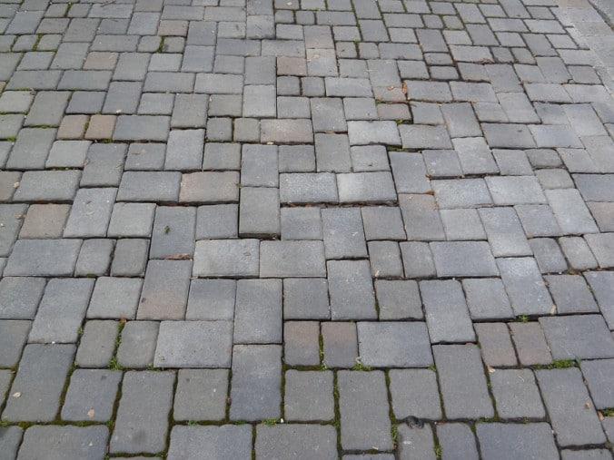 Uneven and sunken grey pavers.
