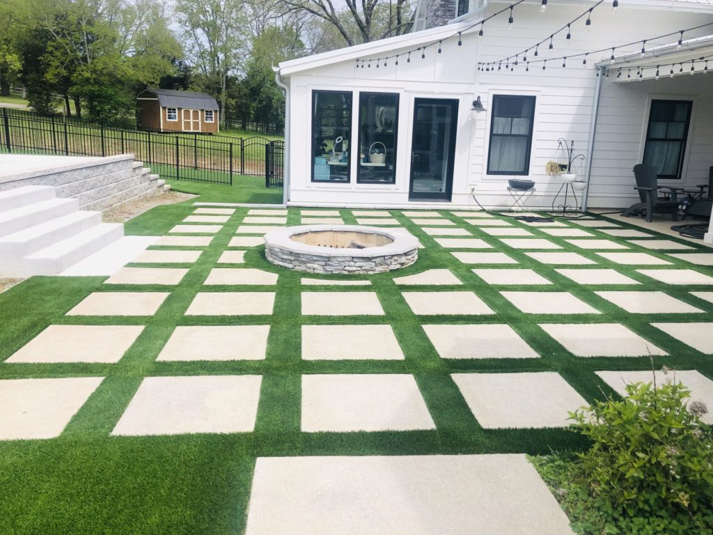 Paver patio with synthetic grass around it.