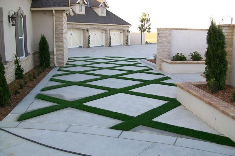 Paver patio with stripes of synthetic grass.