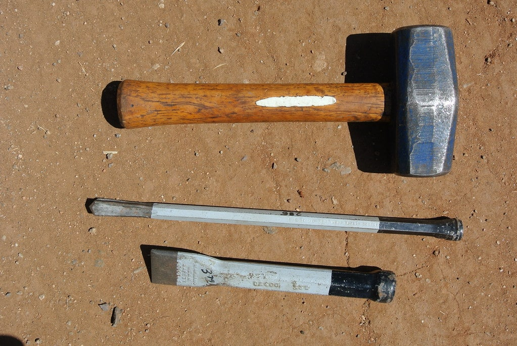 Set of hammer an chisel on the ground.