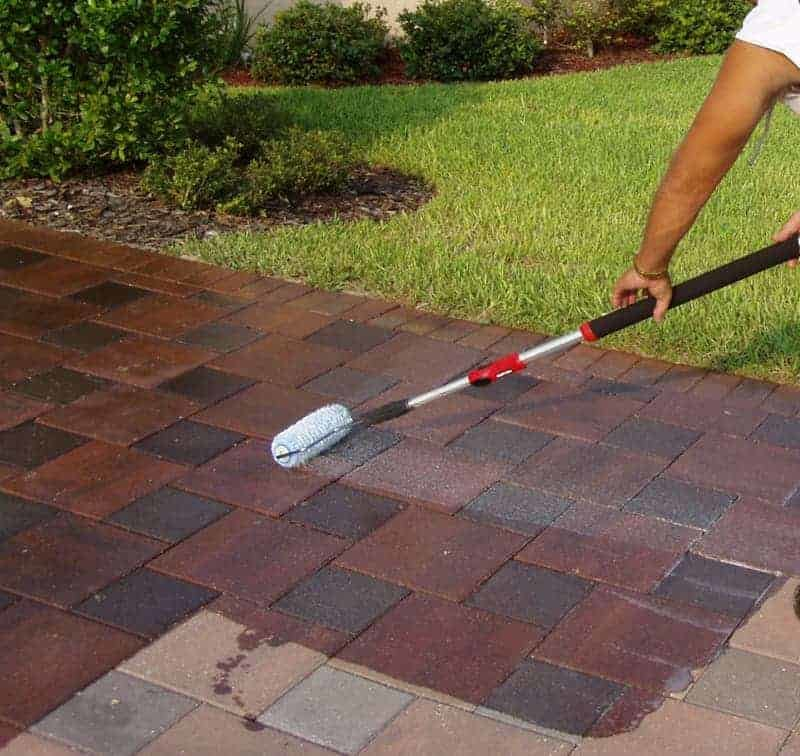 Person applying sealer to a paver patio.