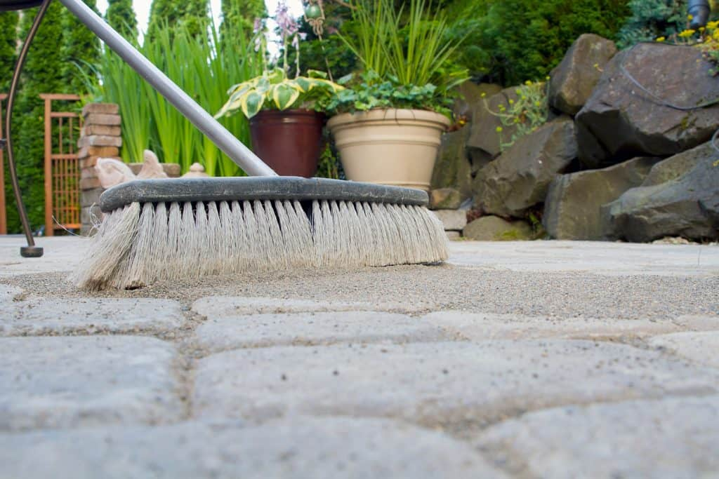 sand being swept on pavers