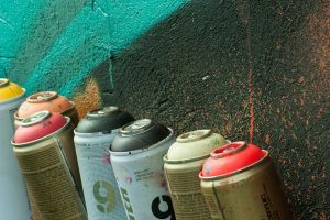 Cans of pray paint next to a painted wall